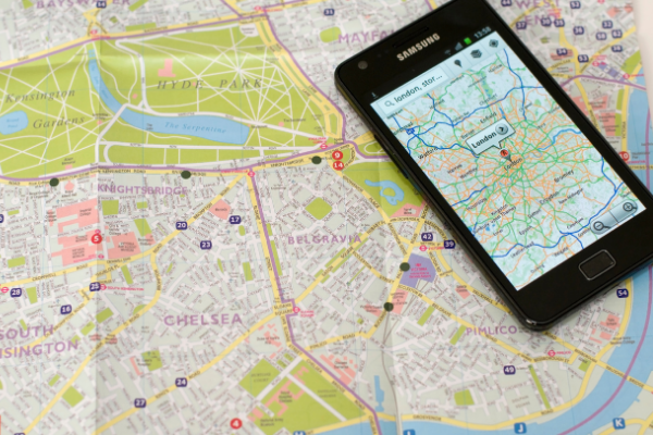 mobile phone showing google maps on top of a paper map
